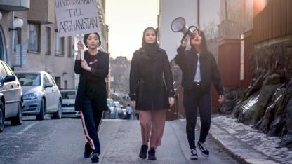 """Tre tjejer går på en gatan. Tjejen till vänster håller en skylt där det står """"Utvisningarna till Afghanistan"""". Tjejen till höger håller en megafon."""